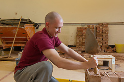 A prisoner learning the building trade in a workshop