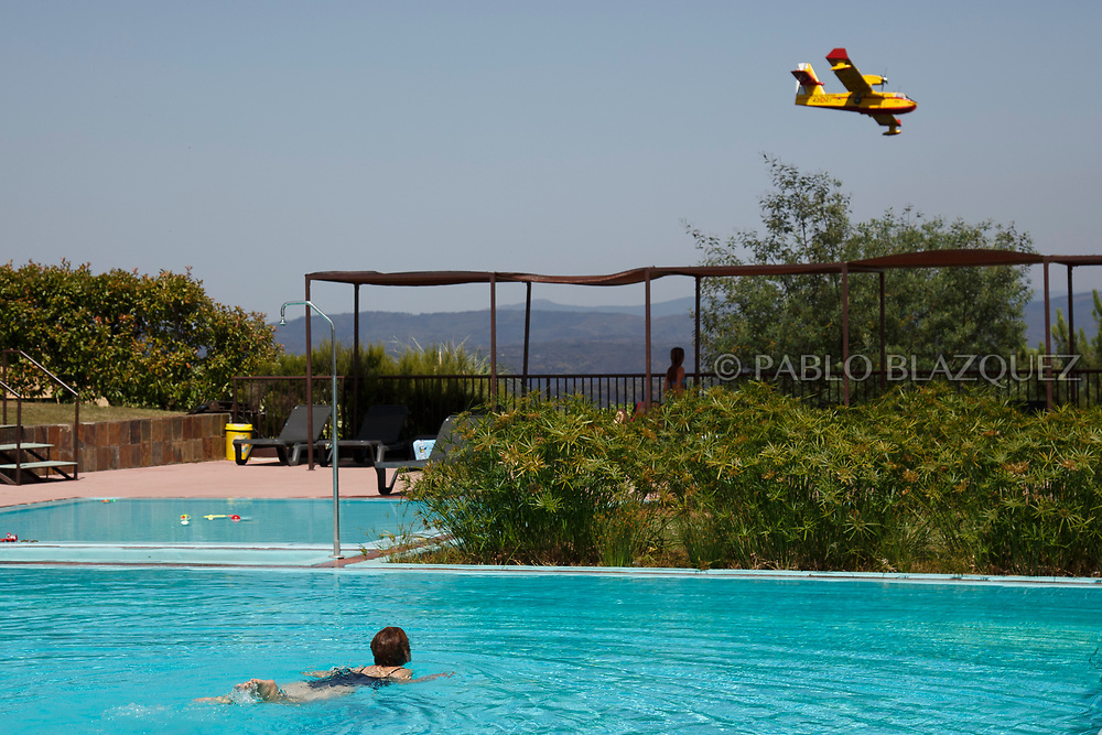 LEIRIA, PORTUGAL - JUNE 20:  A woman enjoys a swim as a firefighter plane flies over after a wildfire took dozens of lives on June 20, 2017 in Mega Fundeira village, near Picha, in Leiria district, Portugal. On Saturday night, a forest fire became uncontrollable in the Leiria district, killing at least 62 people and leaving many injured. Some of the victims died inside their cars as they tried to flee the area.  (Photo by Pablo Blazquez Dominguez/Getty Images)