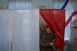 Referendum starts in Crimea. A lady leaves the voting cabin with her vote in Simferopol, . Sunday, 16th March 2014. Picture by Daniel Leal-Olivas / i-Images