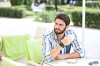 Thoughtful man holding coffee cup at sidewalk cafe