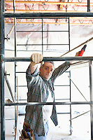 Portrait of contractor with drill standing under scaffolding