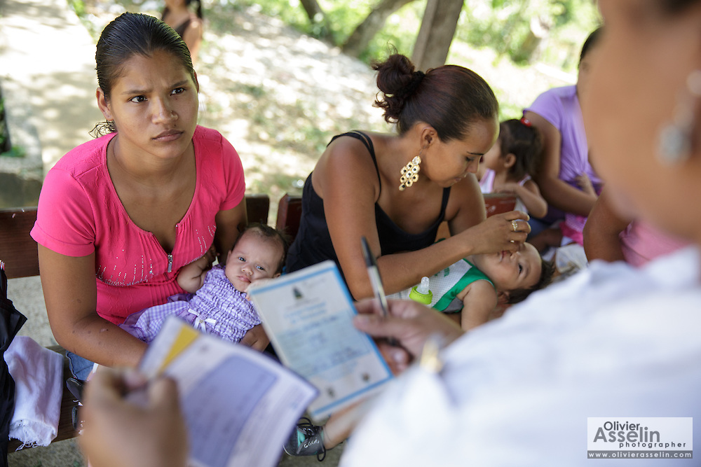 A woman listens to a health worker as she waits to have her child vaccinated during a vaccination session at the primary school in the town of Coyolito, Honduras on Wednesday April 24, 2013.