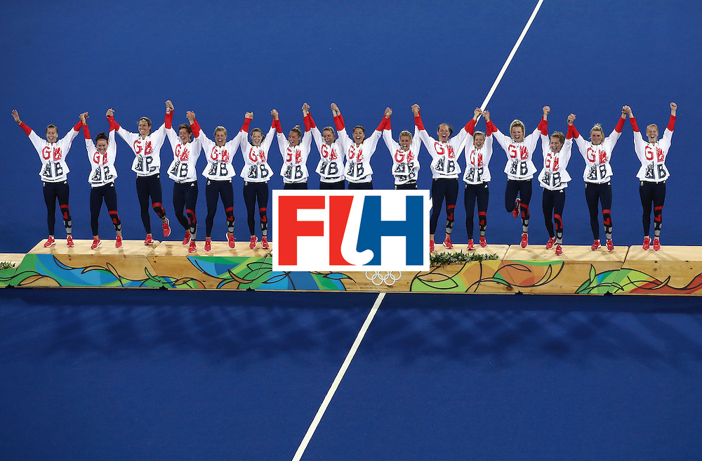 RIO DE JANEIRO, BRAZIL - AUGUST 19:  Team Great Britain pose on the podium during the medal ceremony after defeating Netherlands in the Women's Gold Medal Match on Day 14 of the Rio 2016 Olympic Games at the Olympic Hockey Centre on August 19, 2016 in Rio de Janeiro, Brazil.  (Photo by Mark Kolbe/Getty Images)