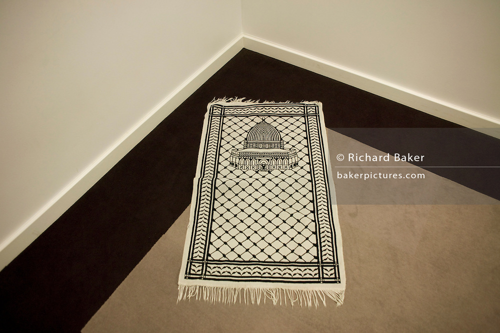 An Islamic prayer mat positioned towards Eastern Mecca in a corner of the Multi-faith room at Heathrow T5.