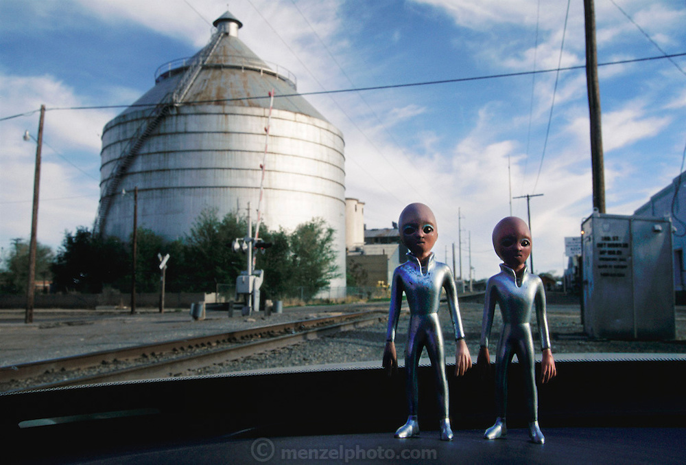 "Alien figures (3"" tall figure sold as ""The Roswell Alien"" by Shadowbox Collectibles, Inc.) tour the area around the storage silos by the railroad tracks, downtown Roswell, New Mexico. The figures are actually sitting on the dashboard of the photographer's rental car. (1997)"
