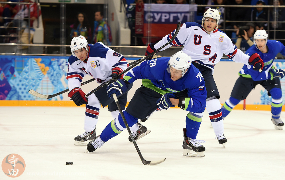Feb 16, 2014; Sochi, RUSSIA; Slovenia forward Jan Urbas (26) chases after the puck ahead of USA forward Zach Parise (9) and forward Patrick Kane (88) in a men's ice hockey preliminary round game during the Sochi 2014 Olympic Winter Games at Shayba Arena.