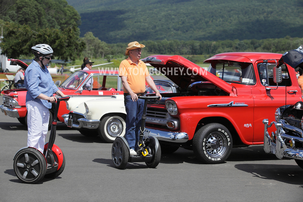 Wurtsboro, NY - An elderly couple riding on Segway Personal Transporters look at a car show at a at Wurtsboro Airport on Aug. 30, 2009.