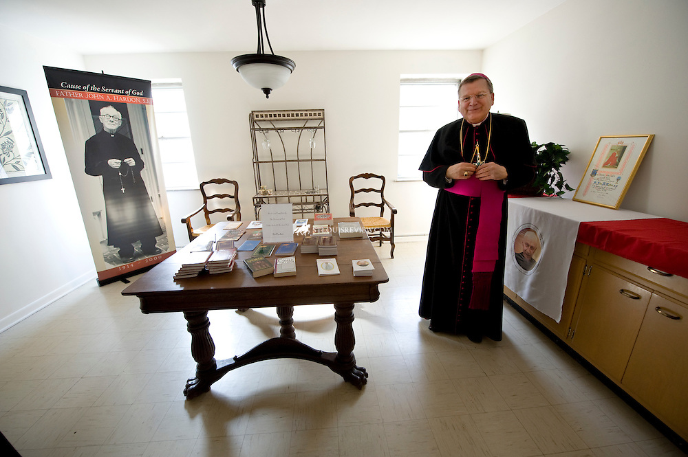 """Archbishop Emeritus of Saint Louis and Prefect of the Supreme Tribunal of the Apostolic Signatura  Raymond L. Burke stands in a room of the Fr. John A. Hardon, S.J., Archive and Guild among a table full of Fr. Hardon's books and writings.    Archbishop Burke initiated the cause for Beatification of Fr. John A. Hardon in St. Louis in 2005 while archbishop of the diocese.  Archbishop Burke was in St. Louis to bless of the archive and guild which is located next to the Cathedral Basilica at 4440 Maryland Avenue.  Fr. Hardon was recognized for his heroic efforts to catechize and to preach the truth """"in season and out of season."""""""