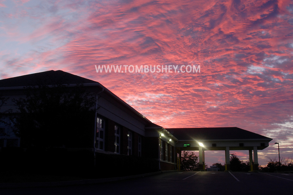 Town of Wallkill, N.Y. - The rising sun turns clouds pink and purple behind the Provident Bank building on Aug. 21, 2006.