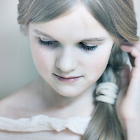 Close up of a young girl with hair in a pony tail looking down