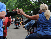 Laura Fong - Alcoholics Anonymous members and supporters 'high five' one another during the annual Founders' Day motorcycle procession to Dr. Bob's gravesite.