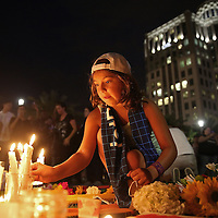 A young girl lights a candle at a makeshift memorial during a vigil at the Dr. Phillips Center for the Performing Arts for the victims of a mass shooting at the Pulse nightclub Monday, June 13, 2016, in Orlando, Florida.  A gunman killed dozens of people in a massacre at the crowded gay nightclub in Orlando on Sunday, making it the deadliest mass shooting in modern U.S. history. (Alex Menendez via AP)