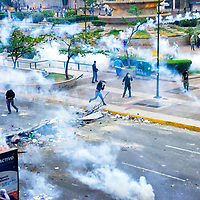 Un grupo de opositores devuelven las bombas lacrimógenas a la policia y guardia nacional en la Plaza Francia de Altamira. Caracas, Venezuela. A group of opponents return the tear gas to the police and national guard in Plaza Francia de Altamira. Caracas Venezuela.