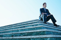 Young man wearing suit sitting on marble platform.