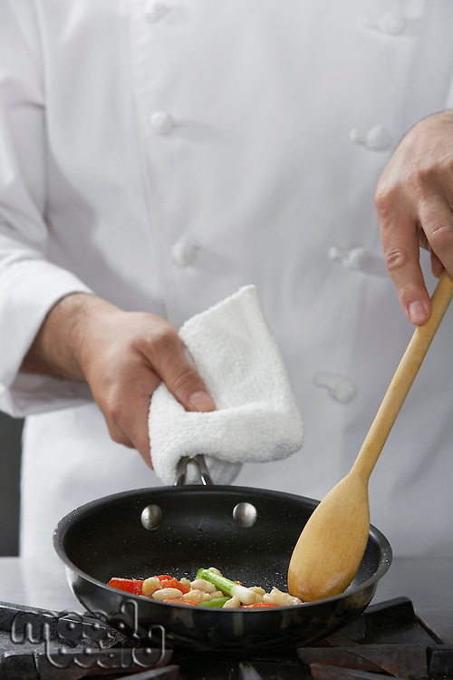 Chef cooking food in frying pan mid-section