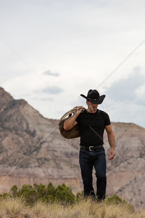 cowboy carrying a duffle bag and lasso outdoors