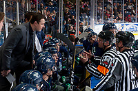 KELOWNA, CANADA - FEBRUARY 23:  Referee Jeff Ingram stands at the board and speaks to Seattle Thunderbirds' head coach Matt O'Dette against the Kelowna Rockets on February 23, 2018 at Prospera Place in Kelowna, British Columbia, Canada.  (Photo by Marissa Baecker/Shoot the Breeze)  *** Local Caption ***