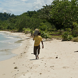 Man carrying a petrol can across the beach.