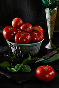 Still life with fresh beefsteak tomatoes and basil on black background.<br />