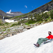 Sledding at Lunch Creek near Logan's Pass in Glacier National Park, Montana. Glacier National Park, Montana.
