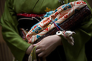 Miehina, a 20 year old maiko ( an apprentice geisha) from the Miyagawacho district of Kyoto, holding her traditional 'kago'- purse, brought into the modern age with the adornment of a small dog toy, Kyoto, Japan, Sunday, May 18th 2008.