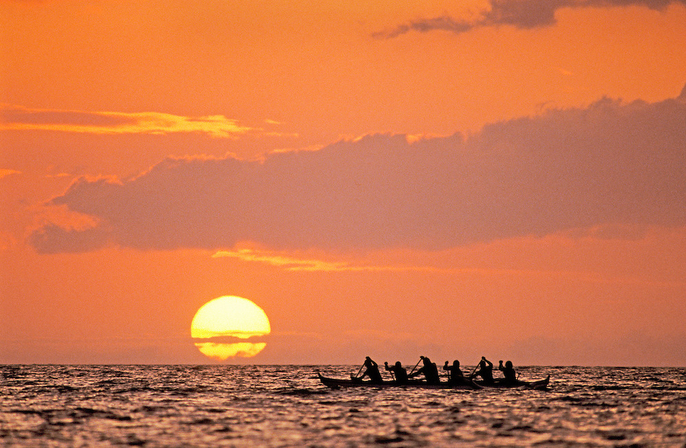 Outrigger canoe paddlers at sunset, Anaehoomalu Bay, Waikoloa, Kohala Coast, Island of Hawaii.