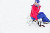 Beautiful young woman sitting on sled