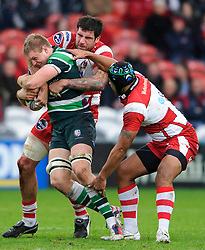 London Irish Flanker (#7) Jamie Gibson is tackled by Gloucester Lock (#5) Jim Hamilton (capt) during the first half of the match - Photo mandatory by-line: Rogan Thomson/JMP - Tel: Mobile: 07966 386802 15/12/2012 - SPORT - RUGBY - Kingsholm Stadium - Gloucester. Gloucester Rugby v London Irish - Amlin Challenge Cup Round 4.