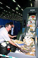 Royal Mail postal worker loading letters into a sorting machine.