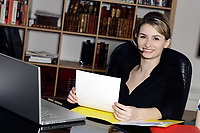 cute and smiling businesswoman at the office desk calling by phone