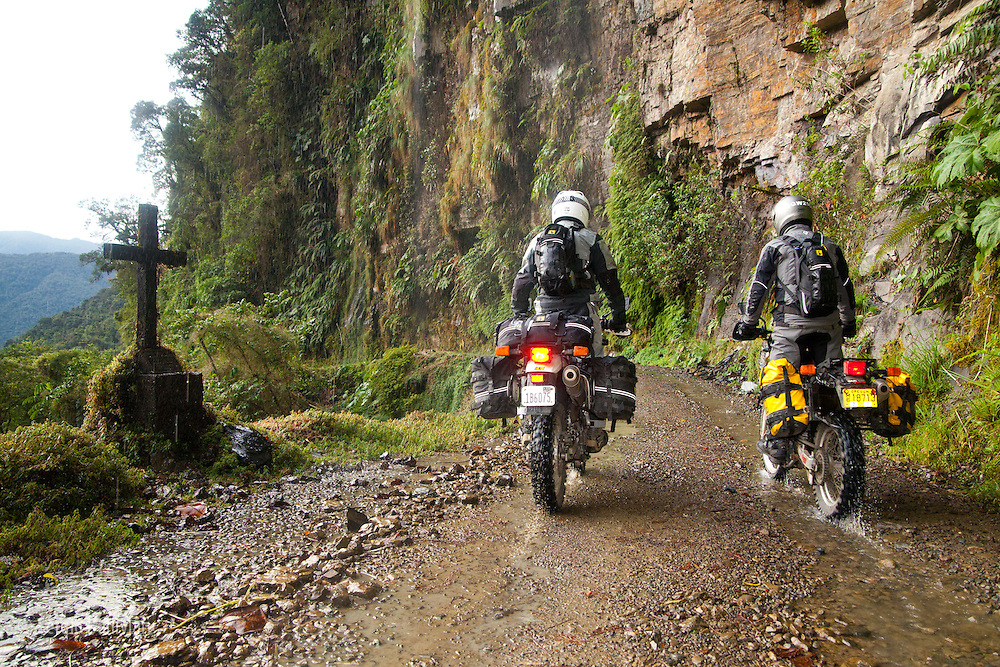 Motorcyclist ride near the edge where a cross marks the spot on the Death Road to Coroico where people fell into the abyss and died in Bolivia.