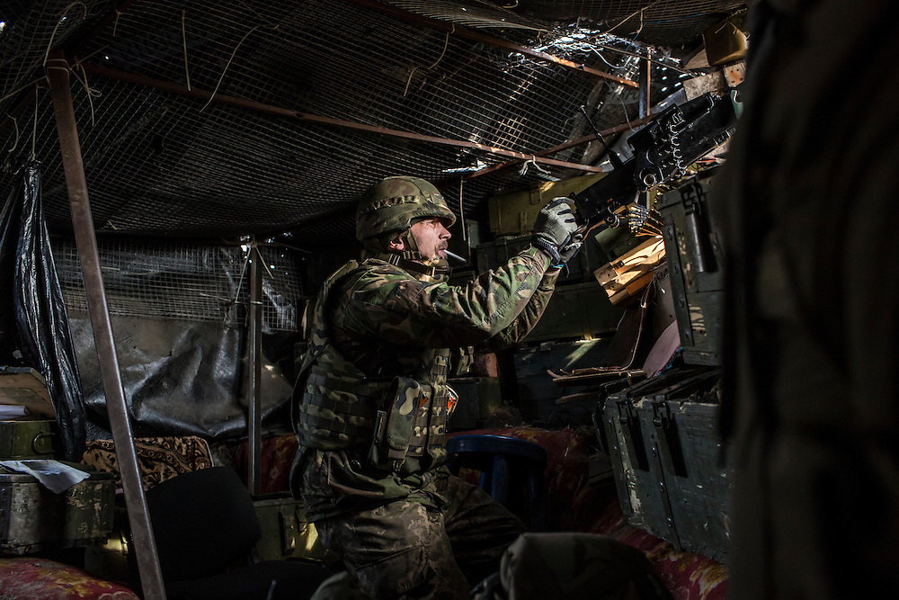 PISKY, UKRAINE - MARCH 20, 2015: Volodya, a fighter for the Dnipro-1 battalion, a pro-Ukrainian militia, operates a .50 caliber rifle in a front-line trench in Pisky, Ukraine. CREDIT: Brendan Hoffman for The New York Times