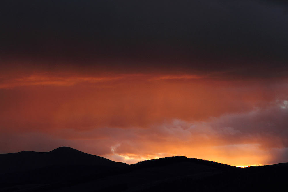 Dramatic skies over Upper Tweeddale in the Scottish Borders as the first snow flurries of late autumn appear during sunset