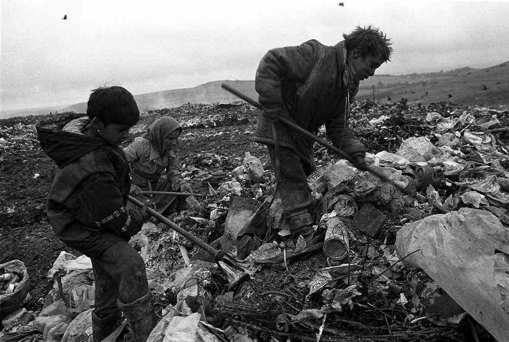 Title: Roma children scavenging anything fit to recycle in order to survive, Pata-Rât Transylvania August 1996.Pata-Rat, a Roma community made up of 150 people living in shacks adjoining a rubbish dump. Transylvania Romania 1996.