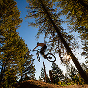 Malachi Artise creates his own bike shadow while grabbing air in a jump line in the Tetons. Parallel Trail.