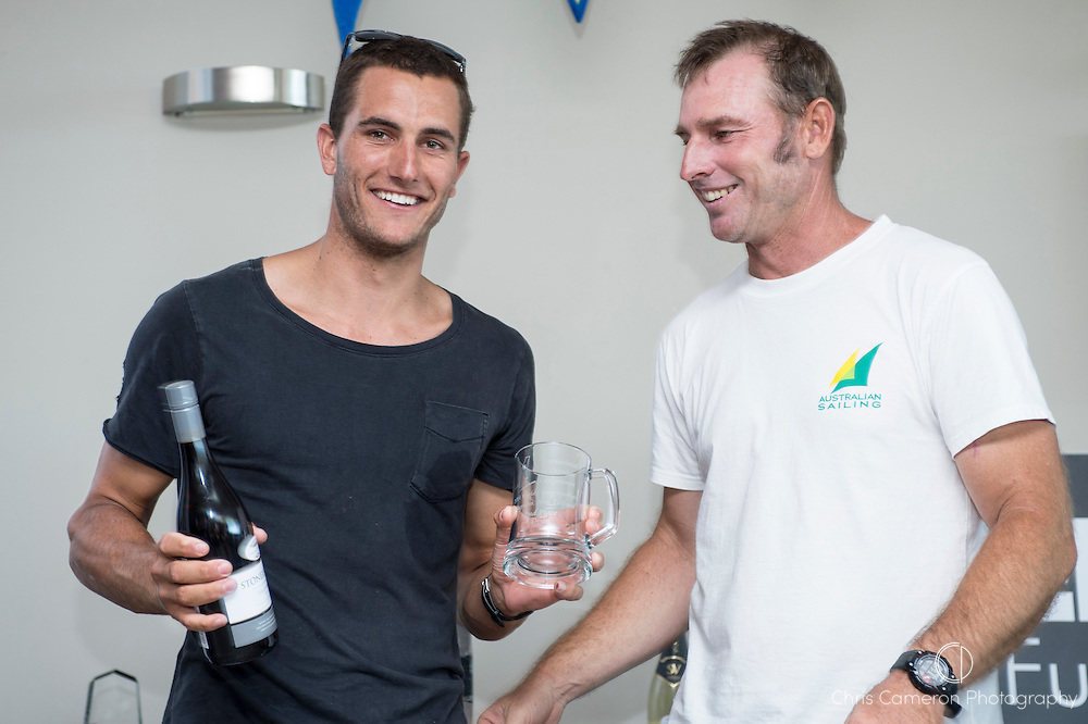 Andrew Landenberger presents Blair Tuke with his trophy for second place.2014 A Class World Championships prize giving. Takapuna Sailing Club, Auckland. 16/2/2014