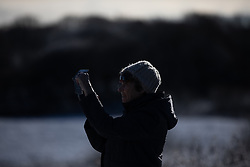 © Licensed to London News Pictures . 23/01/2019. Bolton , UK . A woman takes photos of the landscape on a mobile phone in Horrocks Wood . Clear skies and snow shrouds the hills in the North West as fog descends over Manchester City Centre . Photo credit : Joel Goodman/LNP