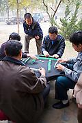 CHINA, BEIJING: Chinese men playing mahjong, a traditional Chinese game of skill and luck using tiles, in a neighborhood park in Beijing as spectators gather to watch.