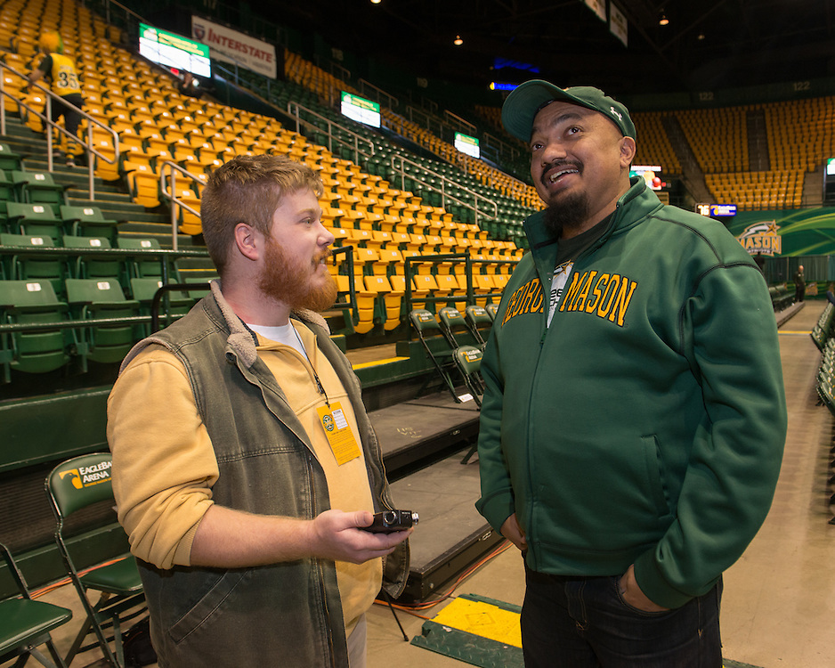 December 5, 2015 - Fairfax, VA - A day in the life of &quot;Doc Nix,&quot; aka Dr. Michael Nickens, the Director of the Athletic Bands for George Mason University. Here he makes comments to a student reporter before the game.<br /> <br /> <br /> Photo by Susana Raab