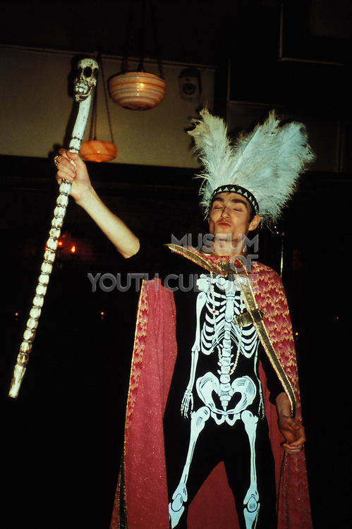 Man in fancy dress holding skull staff, skeleton costume, red cape and feather headset, Hellfire club, London, U.K, 2000.