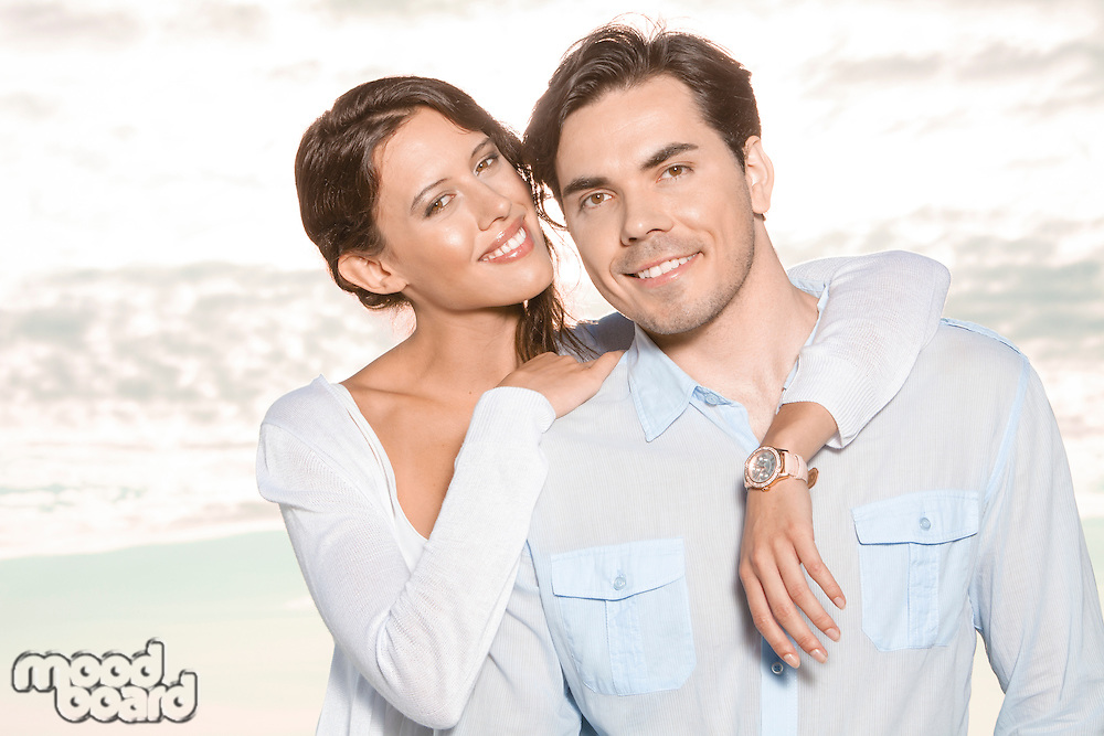 Portrait of happy young woman with arm around man at beach