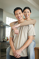 Wife sitting on countertop arms around standing husband