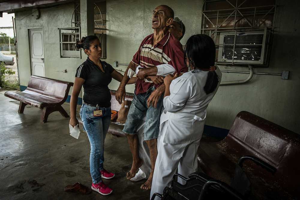 "BARQUISIMETO, VENEZUELA - JULY 29, 2016: A nurse performs the Heimlich maneuver on dementia patient Mario López while he was choking on a piece of food that his daughter, Mayori López, (left) had brought him during a visit.  When nurses couldn't dislodge the food, they called for a doctor, but there was no doctor present.  They they called for an oxygen tank…but there was no oxygen in the hospital either.  They ended up taking him by ambulance to a city hospital that was able to dislodge the food. Mayori said she loves her father, but cannot take care of him - she cannot find all the medicines that he needs because of the shortages..and when he is unmedicated she said he is dangerous and fears he will harm her small children. She has a difficult time finding enough food to feed her family, and feels like her father is better off in the hospital, because at least he gets three meals a day. ""He eats better [in the hospital] than we do…he eats chicken for example, and we don't"" she said.  PHOTO: Meridith Kohut"
