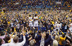 Jan 10, 2017; Morgantown, WV, USA; West Virginia Mountaineers forward Lamont West (15) and West Virginia Mountaineers forward Sagaba Konate (50) stand on the scorers table and celebrate with fans after beating the Baylor Bears at WVU Coliseum. Mandatory Credit: Ben Queen-USA TODAY Sports