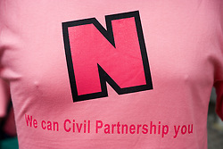 Man wearing pink 'We can Civil Partnership You' Teeshirt at  Nottingham's 2005 Gay Pride Lesbian festival; held at the Arboretum,
