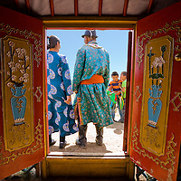 View  from inside a fancy yurt through an ornately decorated doorway of a Mongolian family dressed in traditional clothing and playful children carrying a saddle waring contemporary clothes, Inner Mongolian grasslands, China.