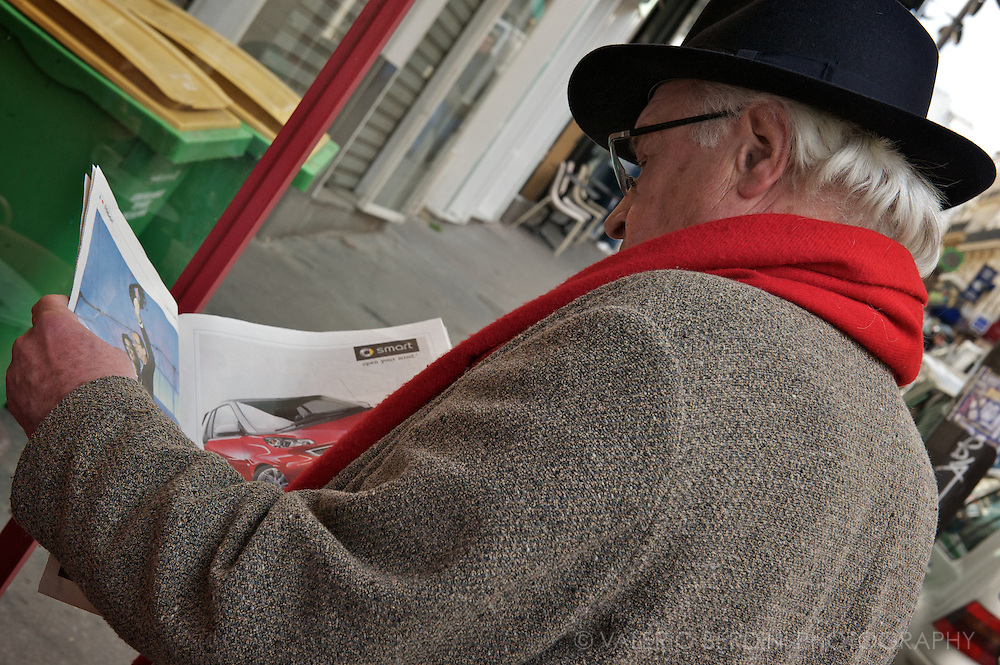 In the streets of Montmartre on Monday morning, a man wear a red scarf and reads the news.