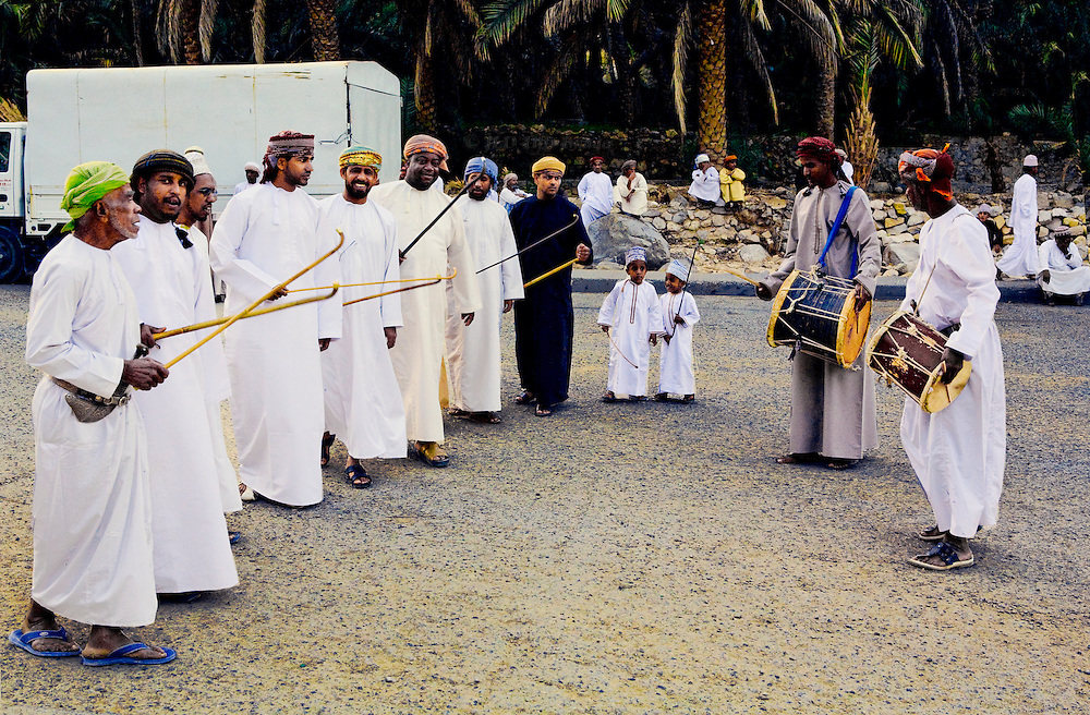Oman, Wadi Bani Khalid.  Two drummers and a row of village men in traditional clothing dance and sing in the street, waving canes,  before a wedding. Two little boys watch their elders, imitating them.