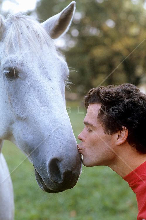 man giving a kiss to a white horse