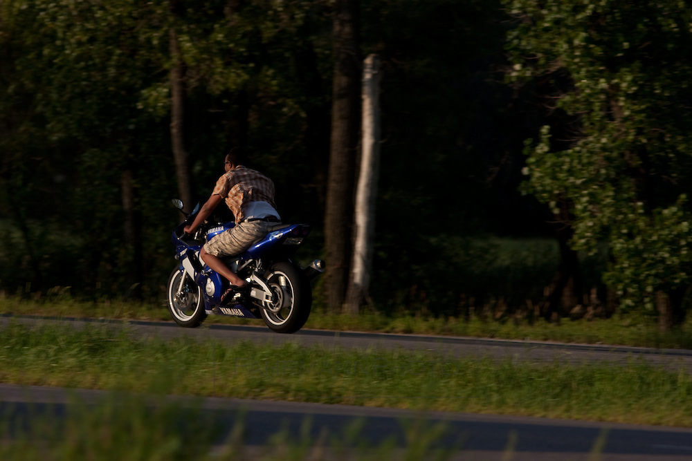 """A man rides a metalic blue motorcyle also called a """"crotch rocket"""" down a highway in Minnesota"""